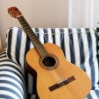 Stock Photo: Acoustic guitar on striped couch