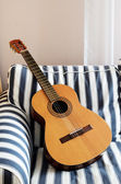 Acoustic guitar on a striped couch — Stock Photo