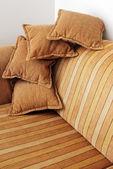 Sofá marrón rayas y cuatro almohadas — Foto de Stock
