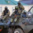 Stock Photo: Armed riot squad wearing masks and helmets sitting on troop-
