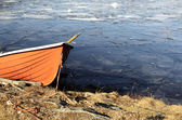 Orange rescue boat on the shore of a frozen lake — Stock Photo