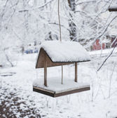 Wooden bird table topped with snow — Stock Photo