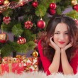 Girl near christmas tree — Stock Photo #17977529