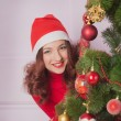 Attractive brunette looking out of Christmas tree - Foto Stock