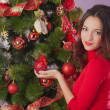 Young girl decorates the Christmas tree - Stock Photo