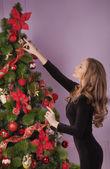若い女の子はクリスマス ツリーを飾る — ストック写真