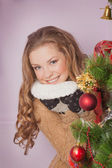 Attractive brunette looking out of Christmas tree — Stock Photo