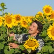 Stock Photo: Farmer standing in sunflower field