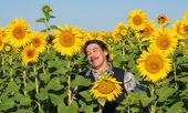 Farmer standing in a sunflower field — Stock Photo