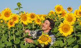 Farmer standing in a sunflower field — Stock Photo