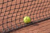 Tennis racket and balls on the clay court — Stock Photo