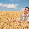 Farmer standing in a wheat field — Stock Photo