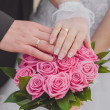 Hands and rings on the wedding bouquet — Stock Photo