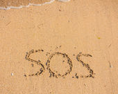 S.O.S written in the sand — 图库照片
