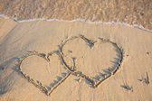 Heart on wet golden beach sand — Stock Photo