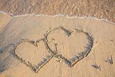 Heart on wet golden beach sand — Stock Photo