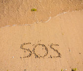 S.O.S written in the sand — Stock Photo