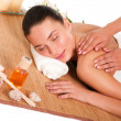 Relaxed beautiful young woman having a spa massage on her back — Stock Photo #12536401