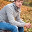 Outdoors portrait of happy young man sitting in autumn park — Stock Photo
