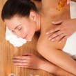 Young woman getting massage in bamboo spa — Stock Photo