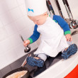 Little baby chef in the cook hat making pancakes — Stock Photo