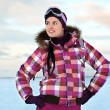 Beautiful young woman wearing skiing suit posing outdoors in win - Stock Photo