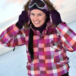 Smiling young woman wearing skiing suit posing outdoors in winte - Stock Photo