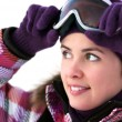 Portrait of smiling happy young woman wearing ski goggles - Stock Photo