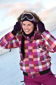 Smiling young woman wearing skiing suit posing outdoors in winte — Stock Photo