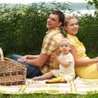 Happy family picnicking outdoors - Stock Photo