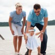 Happy family on the river bank — Stock Photo