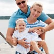 Happy family on the river bank — Stock Photo #13355616