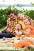 Happy family picnicking outdoors — Stock Photo