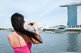 Young woman taking picture of Marina bay hotel in Singapore — Stock Photo
