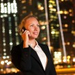 Smiling young business woman talking on the phone in the big cit — Stock Photo #13661964