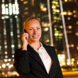 Smiling young business woman talking on the phone in the big cit — Stock Photo