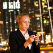 Serious young business woman with the mobile phone in the big ci — Stock Photo