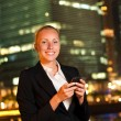 Smiling young business woman with the mobile phone in the big ci — Stock Photo #13661970