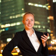 Smiling young business woman with the mobile phone in the big ci — Stock Photo