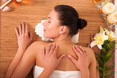 Relaxed beautiful young woman having a spa massage on her back — Stock Photo