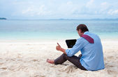 Business man sitting and working on the beach with tablet comput — Stock Photo