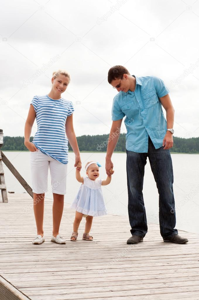 Happy family on the river bank — Stock Photo #14054244