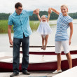 Happy family on the river bank - Stock Photo
