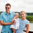 Stock Photo: Happy family on the river bank