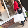 Happy smiling women shopping with white bags looking at the shop — Stock Photo #15840137