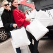 Happy smiling women putting shopping bags into the car  trunk - Lizenzfreies Foto