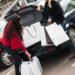 Happy smiling women putting shopping bags into the car  trunk - Stock Photo