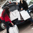 Happy smiling women putting shopping bags into the car  trunk - Zdjęcie stockowe