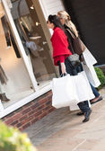 Happy smiling women shopping with white bags looking at the shop — Stock Photo