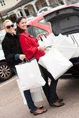 šťastné usmívající se ženy dávat nákupní tašky do kufru auta — Stock fotografie